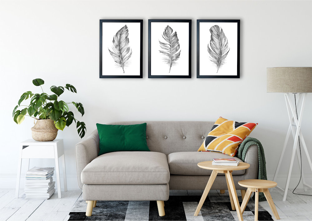szare pióra nad stylową kanapą pod kątem